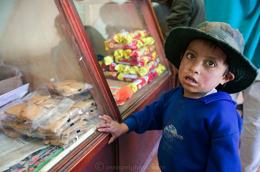 Alvarito Ayme, 4, casts a beseeching look at his mother, Ermalinda, who is buying grain and flour from the local indigenous coop in Simiatug, Ecuador in the hope that she will buy him a sweet from the display counter. His father, Orlando, sold two of his sheep at this weekly market in the indigenous community of Simiatug for $35 US in order to buy potatoes, grain and vegetables for his family. Supporting Image from the book Hungry Planet: What the World Eats.