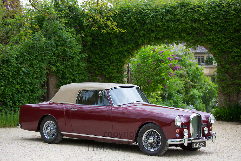 British made Alvis TD21 DHC Series 1 drophead coupe classic car in Peony colour with hood up parked in The Cotswolds, England