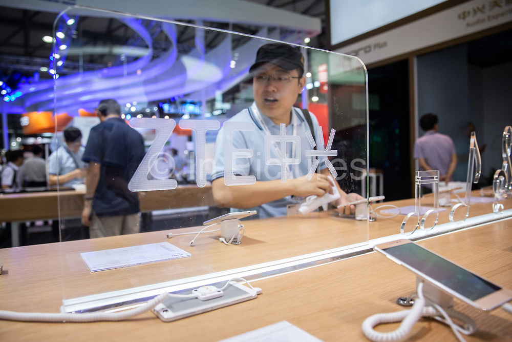 Attendees look at ZTE smartphones on display at the Mobile World Congress Shanghai in Shanghai, China, on Wednesday, June 29, 2016.