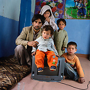Noor Akor, with his children. Lailee, 7, Almos, 5 Jawat, 1.5, Javed, 3, (Farid 12 years old and  Parvees, 10,  his other children and wife are not in the picture )<br />  Noor is not untypical of the average Afghan he has to support his family  on 2-4 dollars a day; he lives on the side of a mountain with no running water, sanitary facilities or schools ( 2.5 hours to the nearest school) it takes him one hour to walk down the hill to his work as a hairdresser.