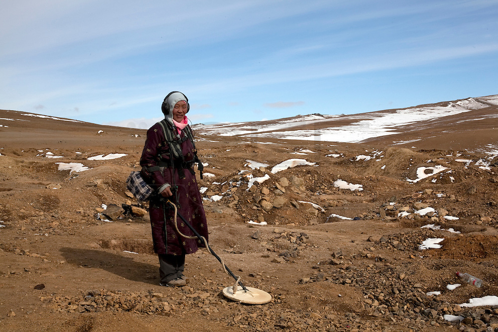Namreh using a metal detector to find gold, Ulan Bulac mining site. Project about illegal gold mining in Mongolia where people from different backgrounds spend their summer and late summer trying to find minerals to get extra money for their lives.