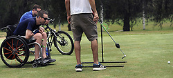 May 24, 2016 - Havana, Cuba - ROBBY BECKMAN (front) 32, watches his shot during a game of adaptive slingshot golf with a pendulum-powered putter (designed by Josh Basile). BRUCE VARNES acts as surrogate body for Robby who broke his neck diving into water and now sailed to Cuba with friends he met initially in rehabilitation for their spinal cord injuries. (Credit Image: © Carol Guzy via ZUMA Wire)