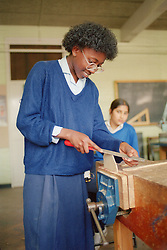 Secondary school girl using file to shape wood held in vice during Design and Technology class,