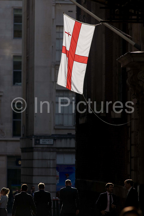 The flag of the City of London hangs in sunlight over gentlemen in the City of London, England UK. Young men walk along this narrow lane, passing below the flag that represents the capital's financial district also called the Square Mile, the oldest quarter of London, founded by the Romans in AD43. The flag of the City of London is based on the flag of England, having a centred red St George's Cross on a white background, with the red sword in the upper hoist canton (the top left quarter). The City is only a tiny part of the metropolis of Greater London, though it remains a notable part of central London. It holds city status in its own right and is also a separate ceremonial county.