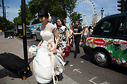Summertime in London, England, UK. Chinese bride out having her photos taken in the very busy area of Westminster where numbers of tourists is the summer increases greatly. Tourism being one of the key income sectors for the UK. The United Kingdom is the world's 8th biggest tourist destination, with more than 30 million visiting each year.
