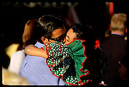 Couple locks in deep kiss amid festival crowd at the Feria de Abril in Seville. Spain