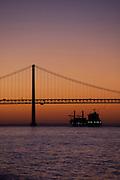 Cargo ship passing under the 25 de Abril Bridge, 25th April Bridge, which crosses the Tagus River in Lisbon, Portugal