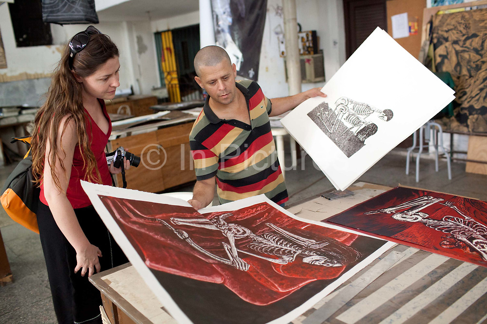 Male Cuban artist showing female tourist his prints for sale. Taller de Experimenta Graphica is a small gallery of independent and emerging artists, specialising in the graphic arts such as printmaking, located next to the Cathedral square placa de la Cathedral it is easy to get to and well worth a look when strolling around Havana old town.