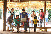 Chief Almir Narayamogo Surui, wearing a google shirt, at a Surui meeting in their traditional meeting hut, where they write up a declaration to defend their land against deforestation. The declaration is written up on his Apple computer<br /> <br /> An Amazonian tribal chief Almir Narayamogo, leader of 1350 Surui Indians in Rondônia, near Cacaol, Brazil, with a $100,000 bounty on his head, is fighting for the survival of his people and their forest, and using the world's modern hi-tech tools; computers, smartphones, Google Earth and digital forestry surveillance. So far their fight has been very effective, leading to a most promising and novel result. In 2013, Almir Narayamogo, led his people to be the first and unique indigenous tribe in the world to manage their own REDD+ carbon project and sell carbon credits to the industrial world. By marketing the CO2 capacity of 250 000 hectares of their virgin forest, the forty year old Surui, has ensured the preservation, as well as a future of his community. <br /> <br /> In 2009, the four clans and 25 Surui villages voted in favour of a total moratorium on logging and the carbon credits project. <br /> <br /> They still face deforestation problems, such as illegal logging, and gold mining which causes pollution of their river systems