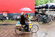 In Utrecht fietst een oudere man door de regen.<br /> <br /> In Utrecht an older man is cycling in the rain.