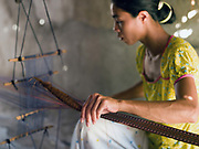 A Hindu Cham woman weaves cotton and silk ribbon with a floor loom outside her home in My Nghiep village, Ninh Thuan province, Central Vietnam. The Cham people are remnants of the Kingdom of Champa (7th to 18th centuries) and are recognised by the government as one of Vietnam's 54 ethnic groups.