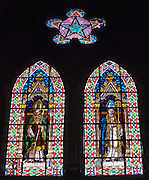 """Stained glass windows, Basilica of the National Vow, Quito, Ecuador, South America. The Basilica of the National Vow (Spanish: Basílica del Voto Nacional) is a Roman Catholic church, neo-Gothic in style, located a few blocks away from Plaza de la Independencia in Quito, Ecuador, South America. Construction began in 1892. Pope John Paul II blessed the Basilica on January 30th, 1985 and in 1988 it was declared immaculate. Although the church was consecrated in 1988, it remains technically """"unfinished."""" San Francisco de Quito, most often called Quito (elevation 9350 feet), is the capital city of Ecuador."""