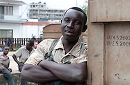 """MWANZA, TANZANIA.  A railway worker who gave his name as """"Matthew"""" pauses for a portrait in a train yard in Mwanza, Tanzania on Friday, September 5, 2014. The workers are part of a crew of laborers who load creosote poles onto railroad cars by hand.  © Chet Gordon/THE IMAGE WORKS"""