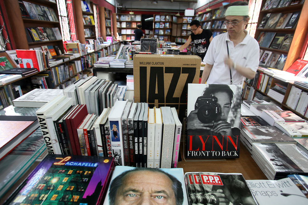 Customers looks through the selection of photography books at the Timezone 8 book shop in Dashanzi.
