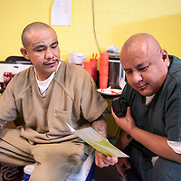 Jaken Shortey, left, and Raymond Becenti, right, read a card given to Randell Benally, one of the current graduates of  the substance abuse treatment program at the McKinley County Adult Detention Center, signed by his fellow classmates in the program and their teachers, Thursday, Jan. 3, 2019 in Gallup.