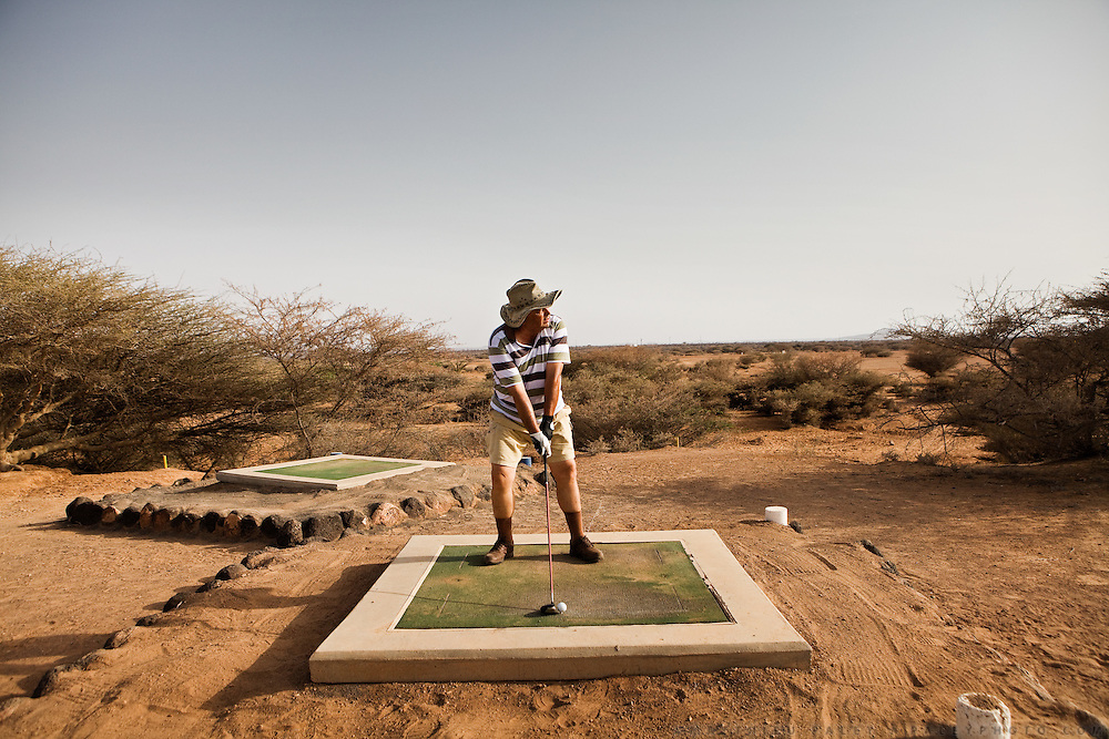 Italian businessman playing golf. A slice of astroturf between a garbage dump and the Somali border makes up Djibouti's golf course. An Italian businessman is teeing off. ..The geostrategical and geopolitical importance of the Republic of Djibouti, located on the Horn of Africa, by the Red Sea and the Gulf of Aden, and bordered by Eritrea, Ethiopia and Somalia.