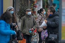 © Licensed to London News Pictures. 14/12/2020. <br /> Sidcup, UK. People waiting at a bus stop. Shoppers in Sidcup High Street, Sidcup in the London borough of Bexley wearing protective face masks as the news breaks that London will go into tier three from Wednesday. Photo credit:Grant Falvey/LNP