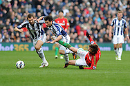 Swansea city's Michu is sent flying by WBA's Gareth McAuley (l) and Claudio Yacob (c). Barclays Premier league, West Bromwich Albion v Swansea city at the Hawthorns stadium in West Bromwich, England on Saturday 9th March 2013.  pic by  Andrew Orchard, Andrew Orchard sports photography,