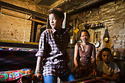 A Nepalese mother sits with her two sons in their family home in Kathmandu, Nepal.  Her older son had been found living on the streets by Voice of Children not-for-profit organisation.  His mother had sent him out to earn money for the family as she had no income.  The organisation have supported this family and enabled the mother to find work so that both her sons can live at home and attend a school education.