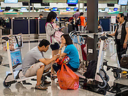 14 AUGUST 2013 - HONG KONG: People wait for information about cancelled flights in Hong Kong International Airport. Dozens of flights were delayed at one of the busiest airports in Asia and Hong Kong raised their alert to level 8, the highest, and closed schools and many businesses because of Severe Typhoon Utor. The storm passed within 260 kilometers of Hong Kong before making landfall in mainland China. Severe Typhoon Utor (known in the Philippines as Typhoon Labuyo) is an active tropical cyclone located over the South China Sea. The eleventh named storm and second typhoon of the 2013 typhoon season, Utor formed from a tropical depression on August 8. The depression was upgraded to Tropical Storm Utor the following day, and to typhoon intensity just a few hours afterwards. The Philippines, which bore the brunt of the storm, reported 1 dead in a mudslide and 23 fishermen missing at sea.   PHOTO BY JACK KURTZ