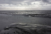 A wide landscape of mudflats at low-tide at Leigh-on-sea, Essex. Mudflats and silted channels are seen in winter under a grey sky, looking towards the power station chimney on the Isle of Grain in Kent, several miles across the Thames where it opens out into the the English Channel after its journey from rural Gloucestershire and through the capital.