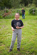 Liana and Parmenter Welty stand holding raspberries at the U-Pick berry patch on the Bradley Orchard farm in Chugiak, Alaska.