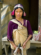 Portrait of a Akha Ya-er woman wearing her traditional headdress at Pak Nam Noi market, Phongsaly province, Lao PDR. One of the most ethnically diverse countries in Southeast Asia, Laos has 49 officially recognised ethnic groups although there are many more self-identified and sub groups. These groups are distinguished by their own customs, beliefs and rituals. Details down to the embroidery on a shirt, the colour of the trim and the type of skirt all help signify the wearer's ethnic and clan affiliations.