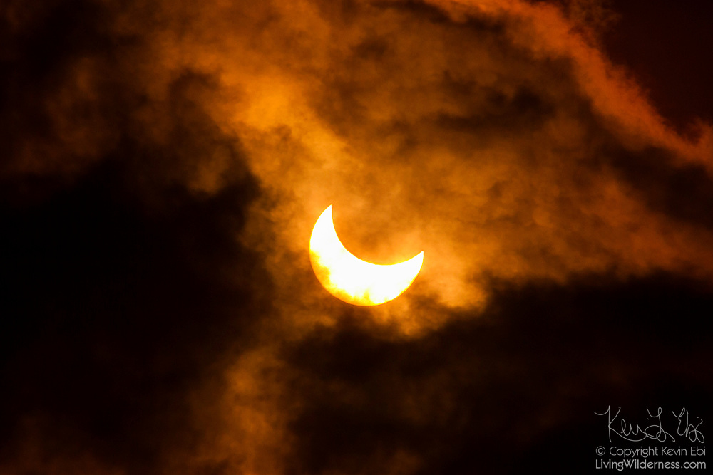 The moon partially eclipses the sun as it passes behind cumulus clouds over Snohomish County, Washington. The October 23, 2014 partial solar eclipse was visible over much of North America.