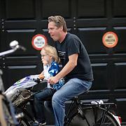 NLD/Amsterdam/20061011 - Thomas Acda haal zijn zoon Paul Finn op van school met de fiets