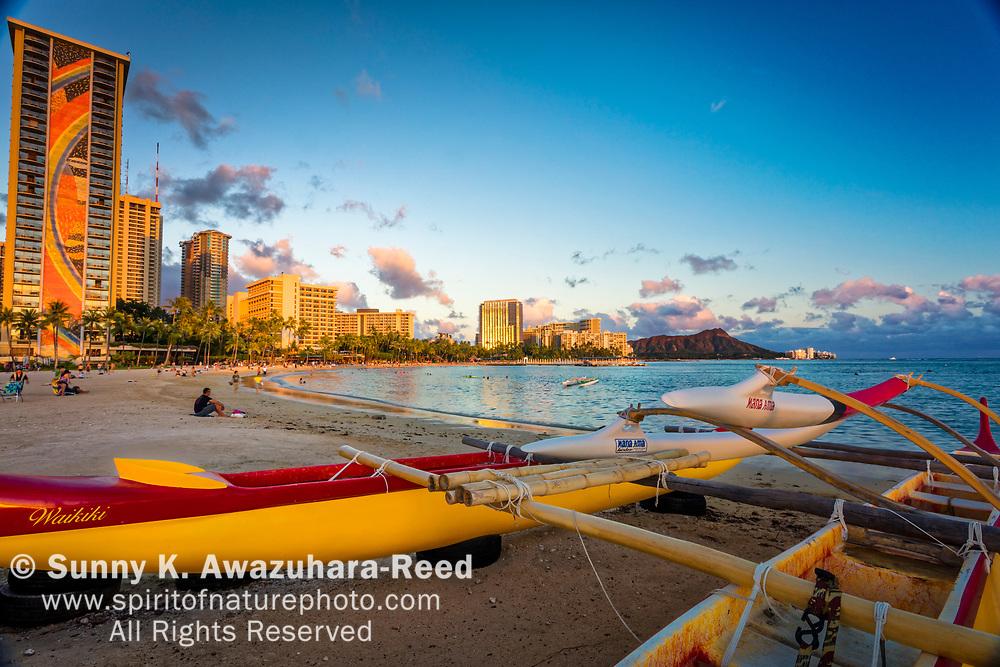 Outrigger canoe on Kahanamoku Beach. Highrise hotels glow in warm sunset light. Diamond Head and Waikiki Beach in the background. Honolulu, Oahu, Hawaii.