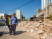 """15 FEBRUARY 2019 - SIHANOUKVILLE, CAMBODIA: Chinese tourists walk past construction debris in one of the casino neighborhoods in Sihanoukville. There are about 80 Chinese casinos and resort hotels open in Sihanoukville and dozens more under construction. The casinos are changing the city, once a sleepy port on Southeast Asia's """"backpacker trail"""" into a booming city. The change is coming with a cost though. Many Cambodian residents of Sihanoukville  have lost their homes to make way for the casinos and the jobs are going to Chinese workers, brought in to build casinos and work in the casinos.      PHOTO BY JACK KURTZ"""