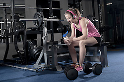 Mid adult woman taking a break after exercising and listening to music in the gym, Bavaria, Germany