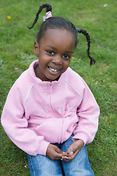 Young girl; sitting on the grass; smiling,