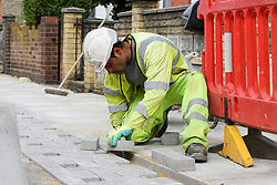 © Licensed to London News Pictures. 11/05/2020. London, UK. A construction worker replacing slabs on a pavement in north London. Prime Minister Boris Johnson in his televised address to the nation from Downing Street has urged construction workers to return to work as he announced a very limited relaxation of the lockdown measures imposed in March to fight the coronavirus. Photo credit: Dinendra Haria/LNP