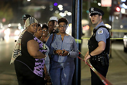 May 5, 2018 - Chicago, IL, USA - A Chicago police officer talks with people at the scene of a shooting outside of the Mount Sinai Hospital emergency room on Saturday, May 5, 2018 in Chicago, Ill. (Credit Image: © Chris Sweda/TNS via ZUMA Wire)