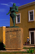 Man walks with his bike in the Square where is the statue of Luiz de Camoes. Camoes was one of the greatest poets in portuguese history and lived in XVI Century. It is believed that he lived in a house in this Square.