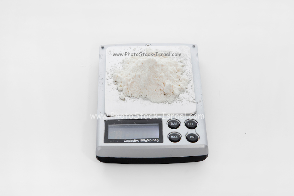 Cutout of an electronic scale used to weigh white powder such as drugs on white background