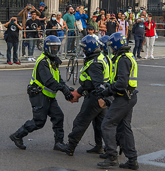 © Licensed to London News Pictures.  24/07/2021. London, UK. A man is detained as police disperse anti-vaccination protesters who block the street in Parliament Square, central London during Freedom Rally.  Photo credit: Marcin Nowak/LNP