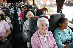 Elderly people out on day trip to the seaside on a coach,