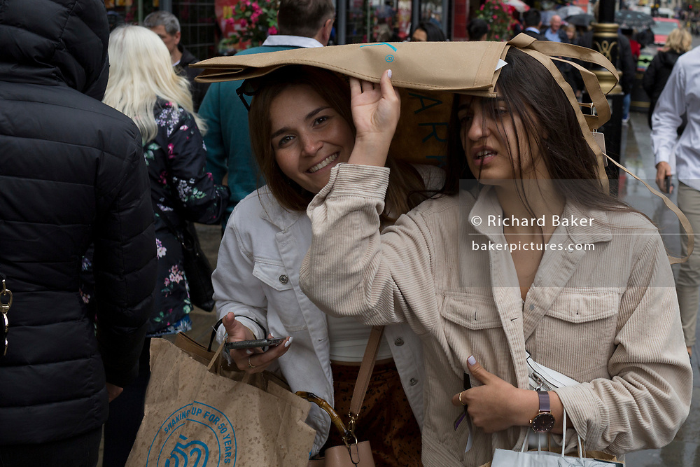 Sheltering under a shopping bag, two women hurry through London's streets during unseasonal June showers, on 15th June 2019, in London, England.