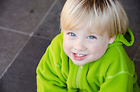 Toddler boy smiling and looking up at camera while shrugging shoulders in Vancouver, Canada.
