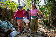 Women carrying a bag of cement during the construction of a path from their village to a local shrine on the 3rd of March 2020 in Raniswara, Ghairung, Gorkha, Nepal.  Construction in small mountain villages is a whole community effort, men and women of all ages work equally to construct paths and roads in the area.