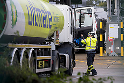 © Licensed to London News Pictures. 04/10/2021. London, UK. A fuel tanker driver gets out of his vehicle at Buncefield oil depot in Hemel Hempstead, Hertfordshire. Military personnel are expected to start helping with driver shortages today following more than a week of long queues and closures at petrol stations. Photo credit: Ben Cawthra/LNP