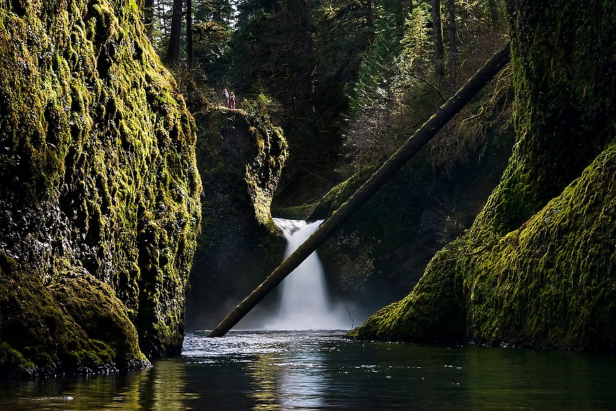 Two people appear tiny, standing on the rim of the gorge overlooking Punchbowl Falls along Eagle Creek Trail, Columbia River Gorge National Scenic Area, Oregon.