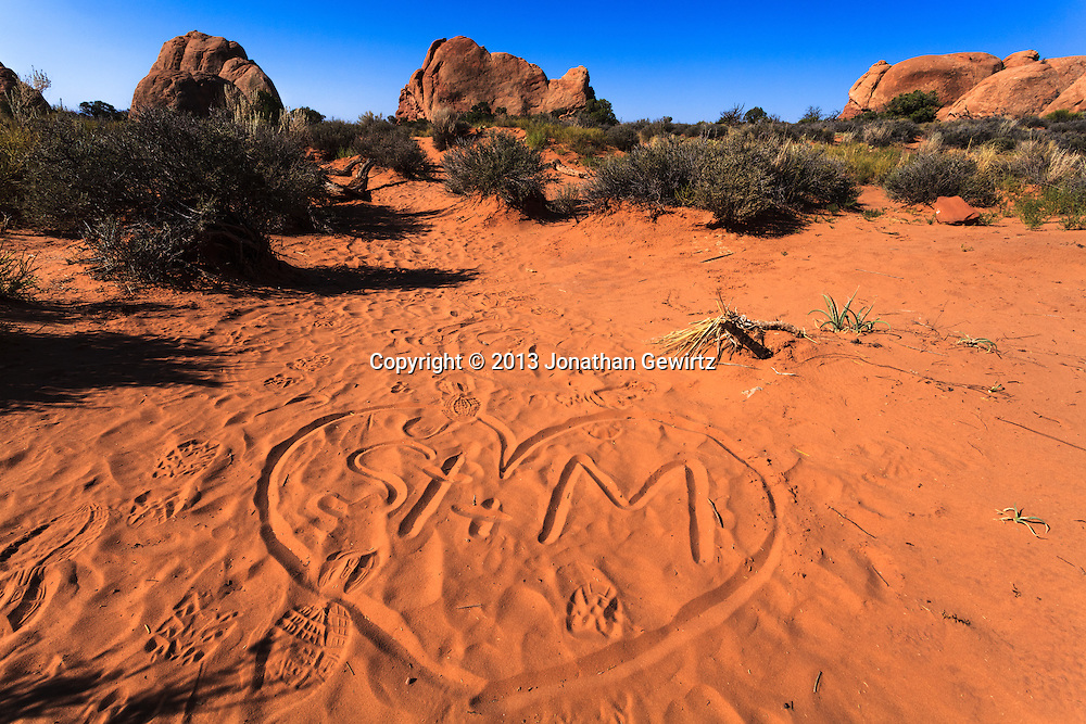 Graffiti and footsteps in the sandy desert floor at Arches National Park, Utah. WATERMARKS WILL NOT APPEAR ON PRINTS OR LICENSED IMAGES.