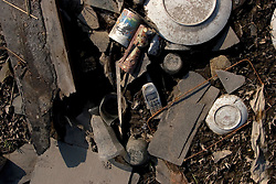 30 Sept, 2005. New Orleans, Louisiana. Lower 9th ward. Hurricane Katrina aftermath.<br /> The remnants of the lives of ordinary folks, now covered in mud as the flood waters remain. A cell phone lies amongst the household items of someone's washed up house.<br /> Photo; ©Charlie Varley/varleypix.com