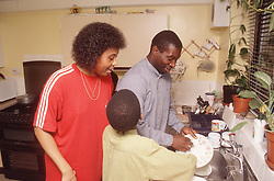 Couple and young son standing in kitchen doing washing up,
