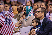 04 JULY 2012 - PHOENIX, AZ:  LUIGE DEL PUERTO holds his son, SOL ELIJAH DEL PUERTO, (right) as they are naturalized US citizens Wednesday. They are originally from the Philippines. About 250 people, from 62 countries, were naturalized as US citizens during the 24th Annual Fiesta of Independence naturization ceremony at South Mountain Community College in Phoenix Wednesday. The ceremony was presided over by the Honorable Roslyn O. Silver, Chief United States District Court Judge.   PHOTO BY JACK KURTZ