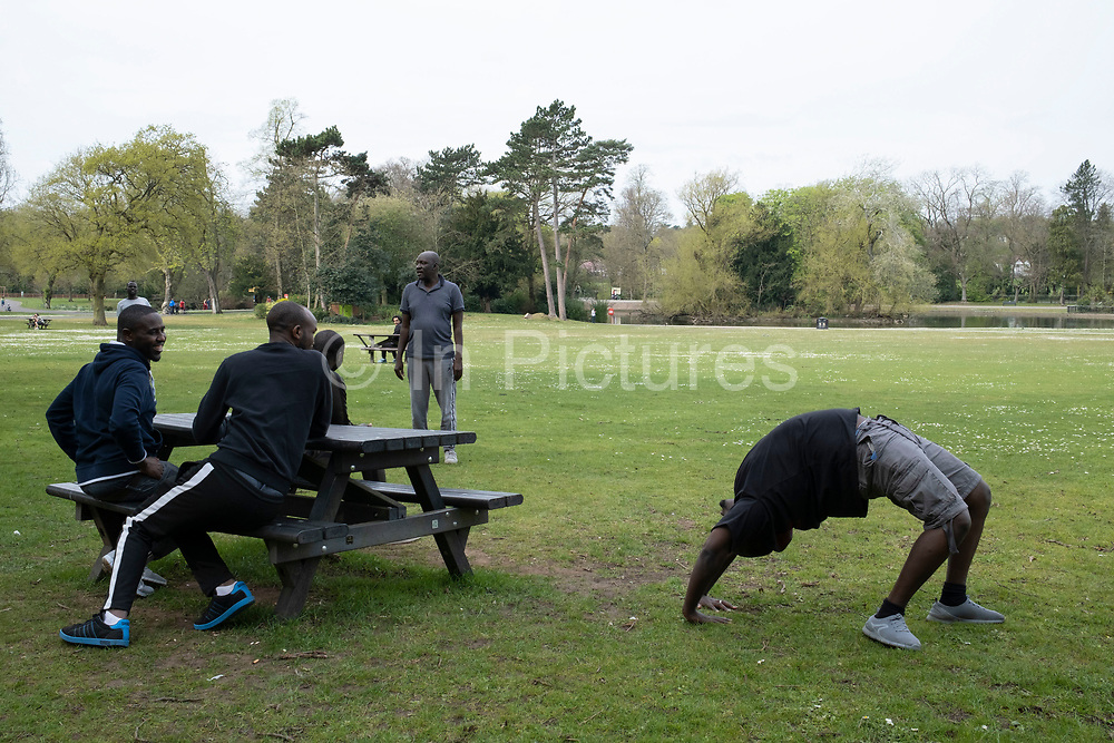 Local people outside hanging out in a close group in Canon Hill Park as Coronavirus is felt on a local level on 12th April 2020 in Birmingham, England, United Kingdom. Coronavirus or Covid-19 is a new respiratory illness that has not previously been seen in humans. While much or Europe has been placed into lockdown, the UK government has announced more stringent rules as part of their long term strategy, and in particular social distancing.