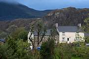 With a backdrop of mountains associated with the slate mining industry, smoke rises from the chimney of a property, on 2nd October 2021, in Blaenau Ffestiniog, Gwynedd, Wales. The derelict slate mines around Blaenau Ffestiniog in north Wales were awarded UNESCO World Heritage status in 2021. The industry's heyday was the 1890s when the Welsh slate industry employed approximately 17,000 workers, producing almost 500,000 tonnes of slate a year, around a third of all roofing slate used in the world in the late 19th century. Only 10% of slate was ever of good enough quality and the surrounding mountains now have slate waste and the ruined remains of machinery, workshops and shelters have changed the landscape for square miles.